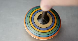 Close up shot of a spinning top moving on a silver surface...