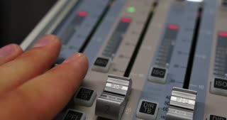 Close up shot of an audio mixer and a man pulling up the knobs, the shot is moving from left to right...