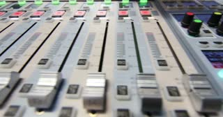 Close up shot of an audio mixer, the knobs are being pulled up and down, the shot moves from right to left...