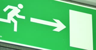 Close up shot of an emergency exit sign, the shot goes out of focus and comes back into focus