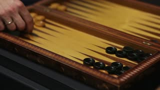 Close up side angle footage of two players playing backgammon