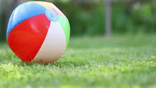 Footage of a beach ball lying on a grass field, the summer has come...