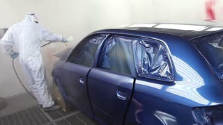 Footage of a blue car being varnished in a painting chamber...