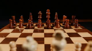 Footage of a chess board and its pieces lined up, the shot is taken behind white pieces looking into black ones...