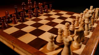 Footage of a chess board and its pieces lined up, two kings are being brought to the front...