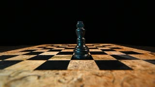 Footage of a chess board in a dark room with a black king on the board standing, white king hits the black king and takes his place, in slow motion...