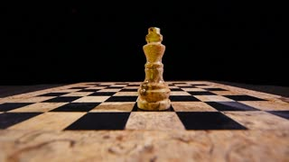 Footage of a chess board in a dark room with a white king on the board standing, black king hits the white king and takes his place, in slow motion...