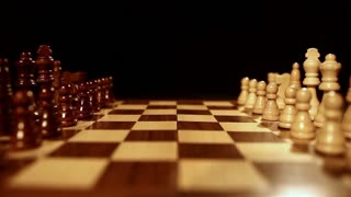 Footage of a chess board ober a black background, two kings being put in the middle of the chess board...