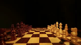 Footage of a chess board over a black background, the shot moves from the top to the bottom of the chess board...