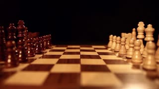 Footage of a chess board with it´s pieces lined up on it, a person starts the game with a pawn...