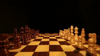Footage of a chess board with it´s pieces lined up on it, the shot is moving slowly down...