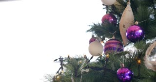 Footage of a christmas tree with purple and white balls on it