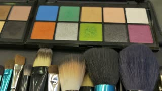 Footage of a colorful make-up palette and a lot of brushes lying on the table, the shot is moving from right to left...