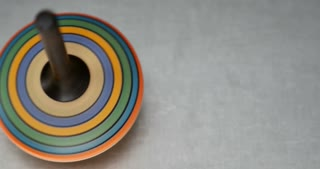 Footage of a colorful spinning top on a metal table...