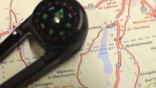 Footage of a compass lying on a road map, the shot is moving from the bottom to the top...