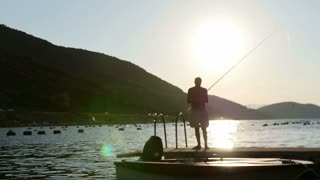 Footage of a fisherman fishing on a pier near a beach...