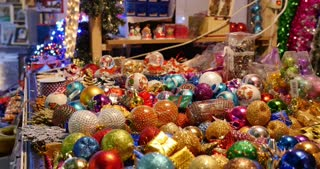 Footage of a christmas market, a lot of colorful balls being sold, the shot is moving from right to left...