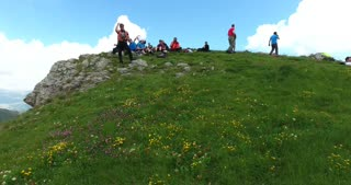 Footage of a group of hikers taking a rest on the top of a mountain...