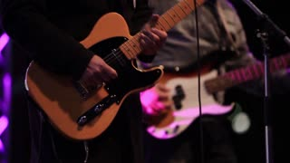 Footage of a guitar and bass guitar players - the focus goes from one to another