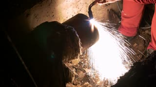 Footage of a intervention worker preparing a ruptured heating system pipe for welding...