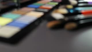 Footage of a make up palette with a lot of various brushes lying in front of it, the shot is coming into focus...