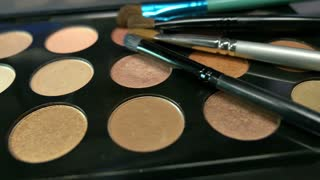 Footage of a make-up palette with some brushes lying on the top of it, the shot is moving from one side to the other...