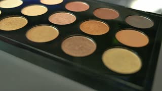 Footage of a make-up palette with three brushes lying beside it, the shot is moving from one side to the other and vice versa...