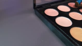 Footage of a make-up palette with three brushes lying on the top of it, the shot is moving from one side to the other...