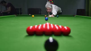 Footage of a man breaking the balls at a snooker game...