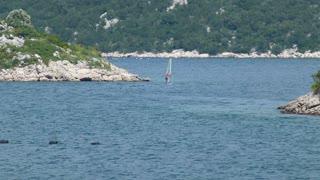 Footage of a man enjoying in windsurfing near a beach...
