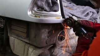 Footage of a man grinding a part of the car and preparing it for a general repair...