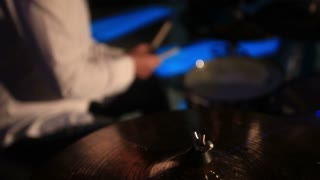 Footage of a man playing drums at a concert...