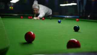 Footage of a man playing snooker, he hits the red ball but misses the hole...