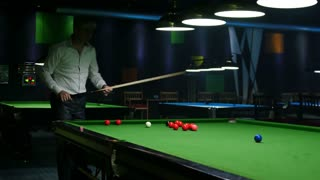 Footage of a man playing snooker in an entertainment center...