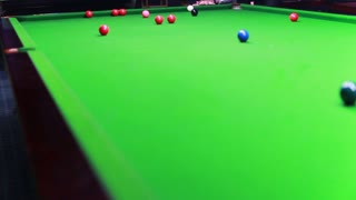 Footage of a man playing snooker, the shot is moving from the bottom...