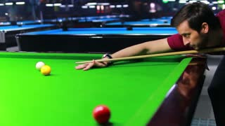 Footage of a man playing snooker, the shot is moving from the right to the left...