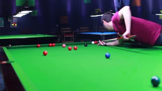 Footage of a man playing snooker, the shot is moving from the top to the bottom...