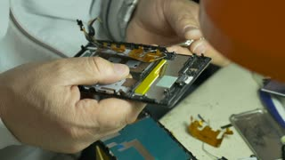 Footage of a man repairing a broken cell phone in a cell phone service...