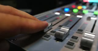 Footage of a mans hand pulling up the knobs of an audio mixer...