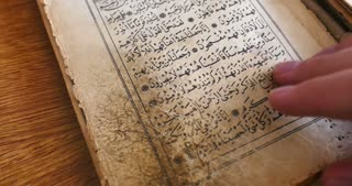 Footage of a person leafing through an old Quran...
