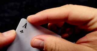 Footage of a person revealing his cards, he has got four aces, isolated on a black background...