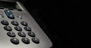 Footage of a phone on a black background and a hand dialing 911