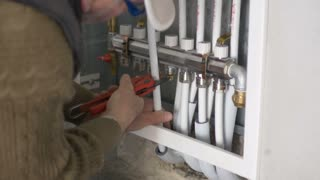 Footage of a plumber working on a central heating system in a new home...
