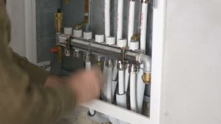 Footage of a plumber working on a central heating system in an apartment...