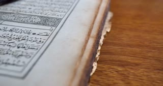 Footage of a Quran lying on a table with reading glasses on it and a tasbeeh in the back, the shot is moving from the right to the left...