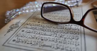 Footage of a Quran lying on a table with reading glasses on it and a tasbeeh in the back, the shot is moving from the left to the right...