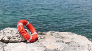 Footage of a red rescue buoy leaned on a stone on a pier - time lapse...