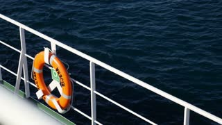 Footage of a rescue buoy hanging on the ship fence while the ship is moving..
