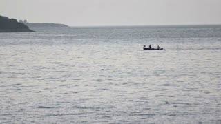 Footage of a sea and a boat with two people in it passing by