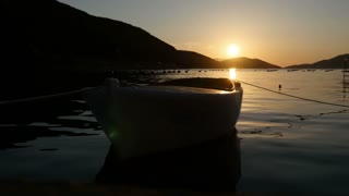 Footage of a small wooden boat swinging on a sea, filmed during a sunset